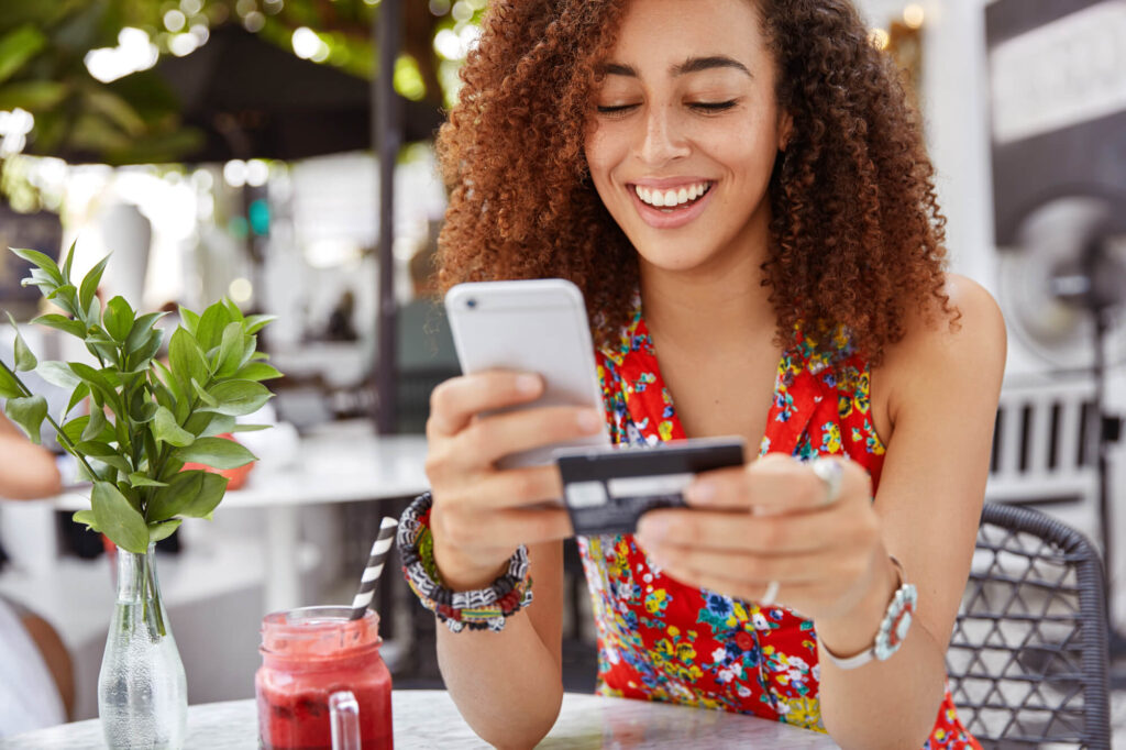 woman holding credit card and cell phone
